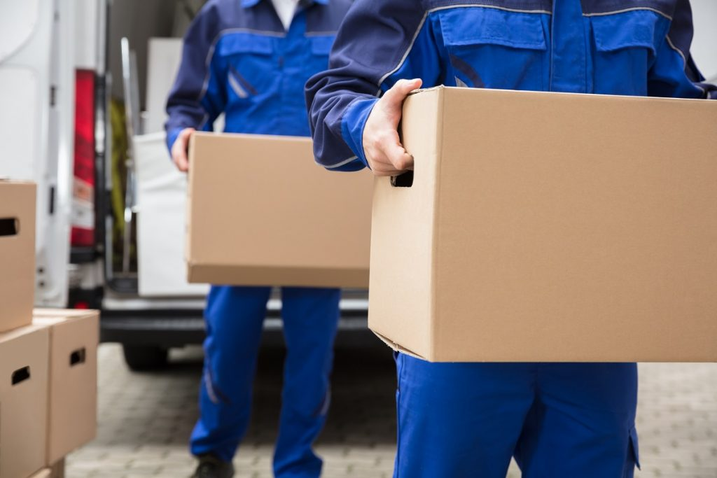 Movers in blue unloading the truck
