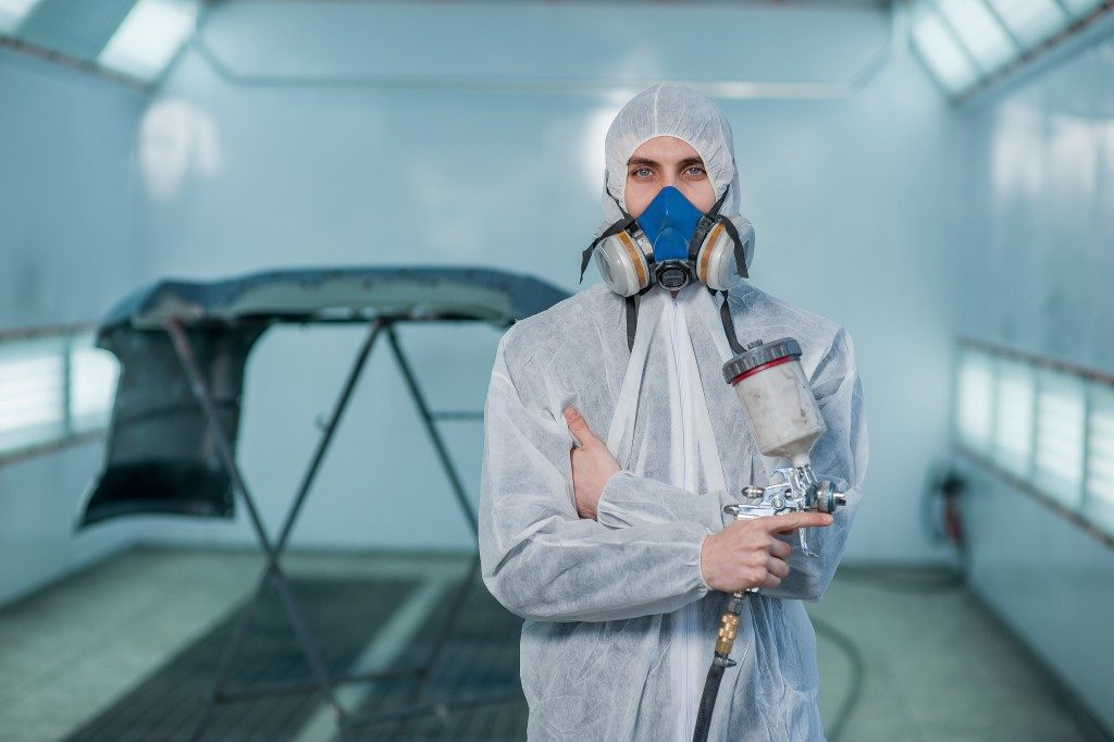 man prepping in paint spray booth