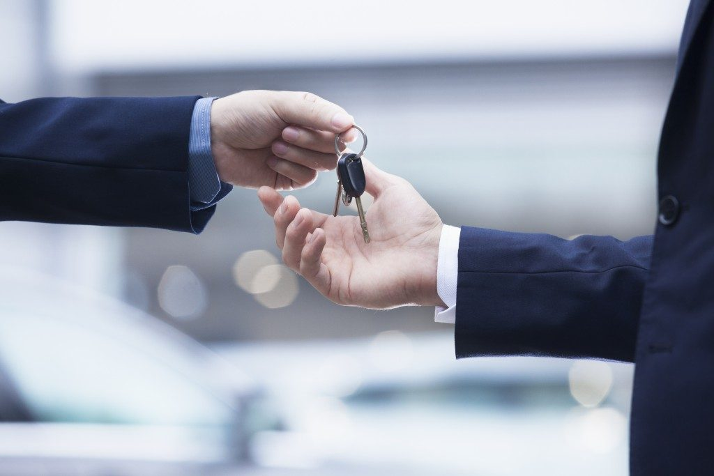 car rental serviceman handing keys over to customer