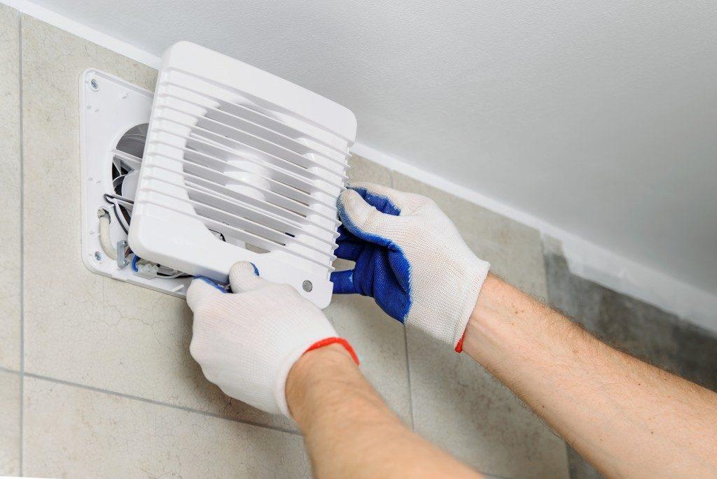 Person installing an exhaust fan