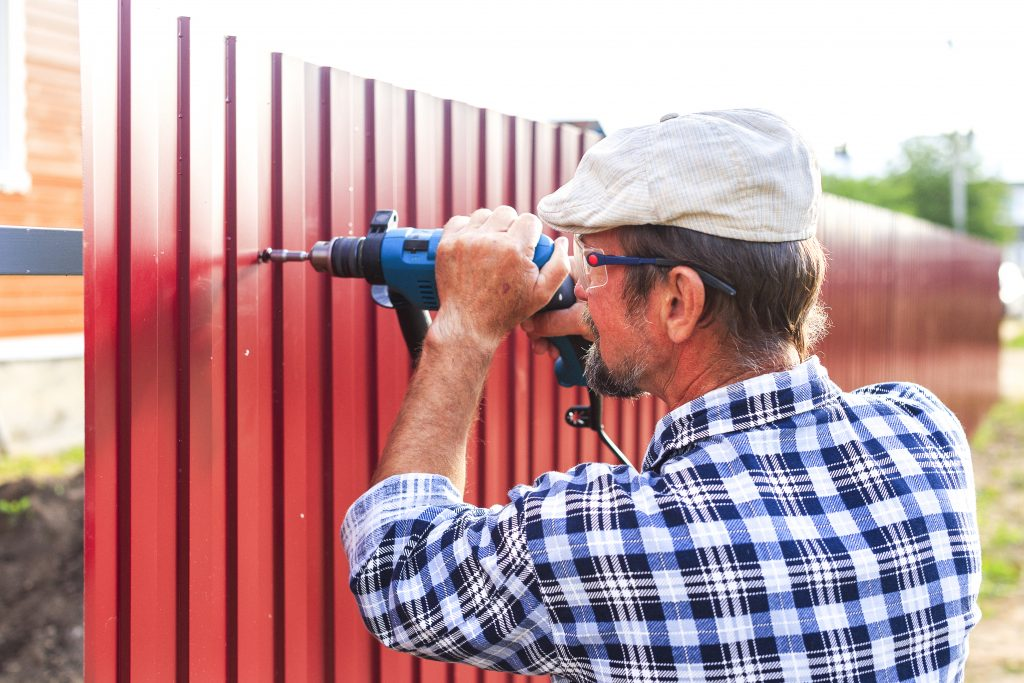 man installing metal fence
