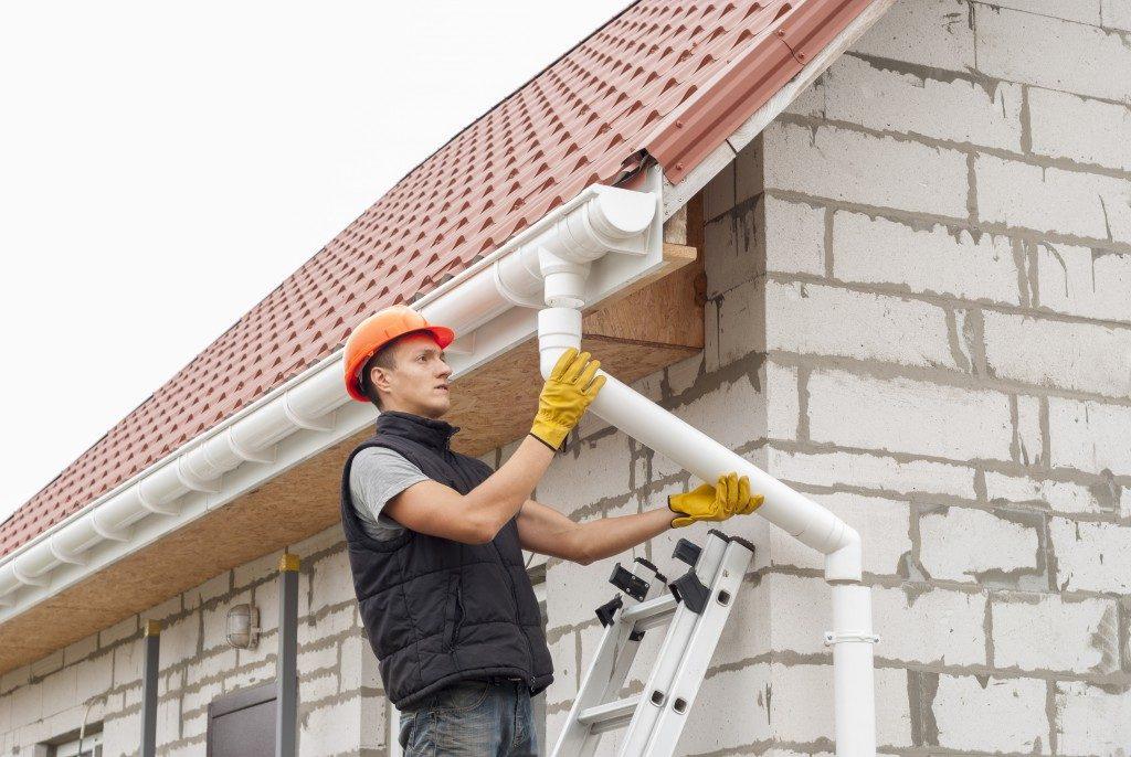 man repairing gutter