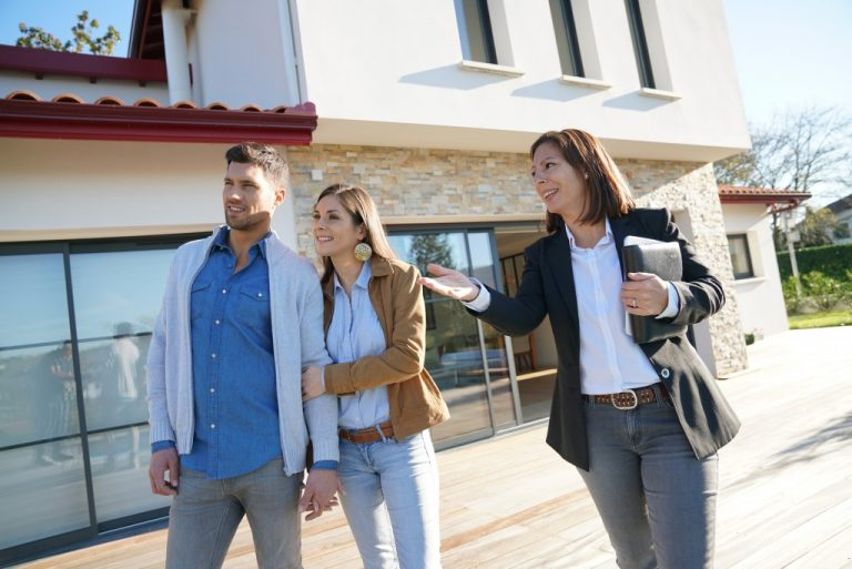 couple looking at houses with agent