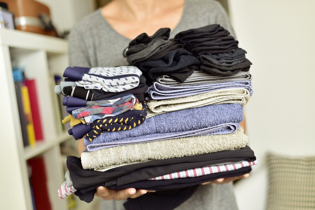 Holding a pile of folded clothes