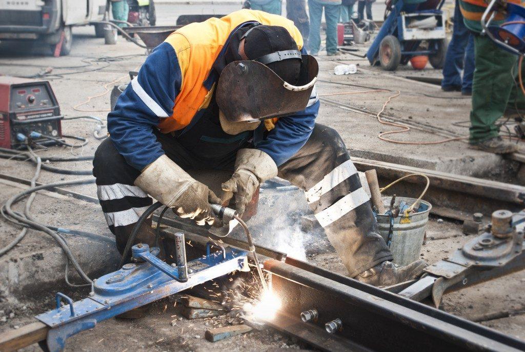 man welding track