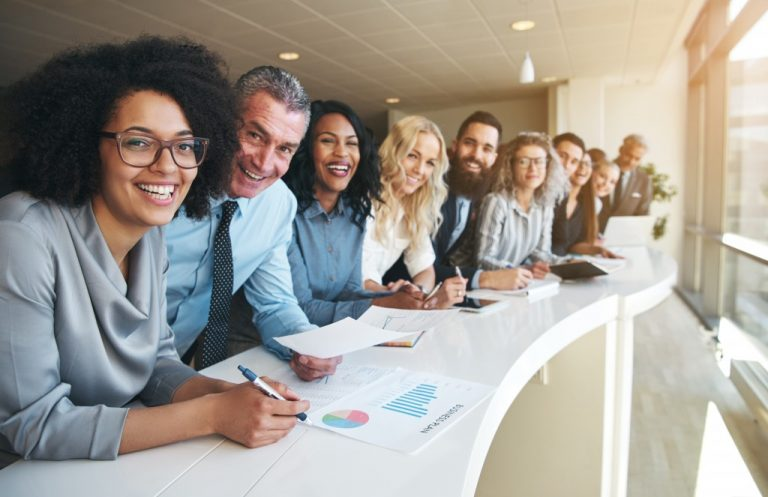 line of smiling employees standing at the side of white table