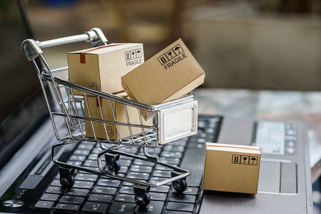 A mini representation of an online store cart filled with boxes on top of a laptop