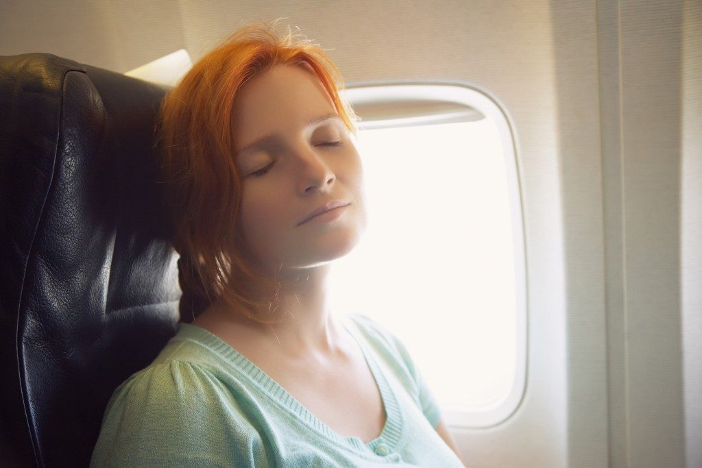 sleeping woman in the chair on board the aircraft