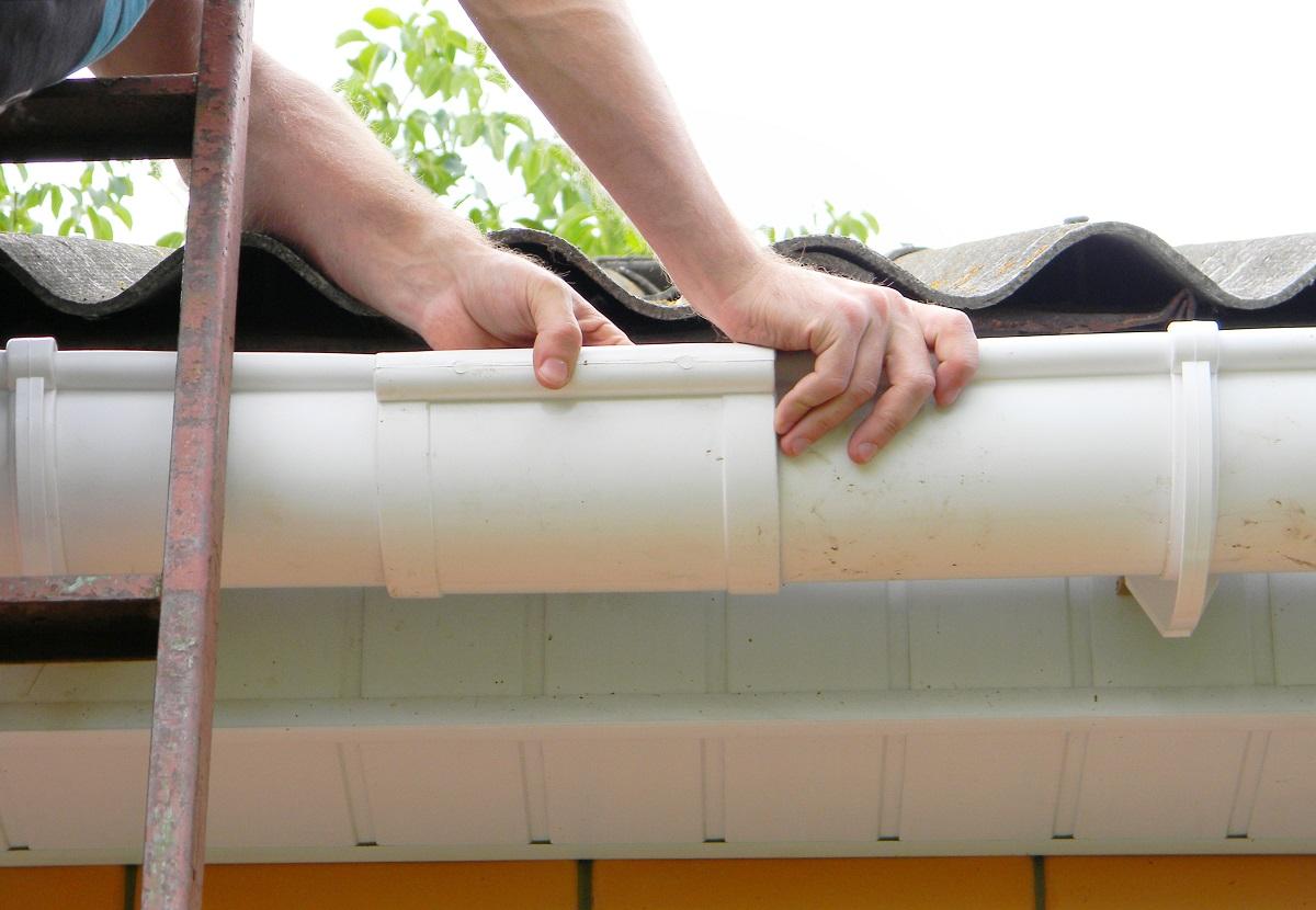 Man fixing roof gutter