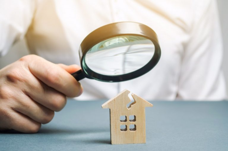 looking at old house model with magnifying glass