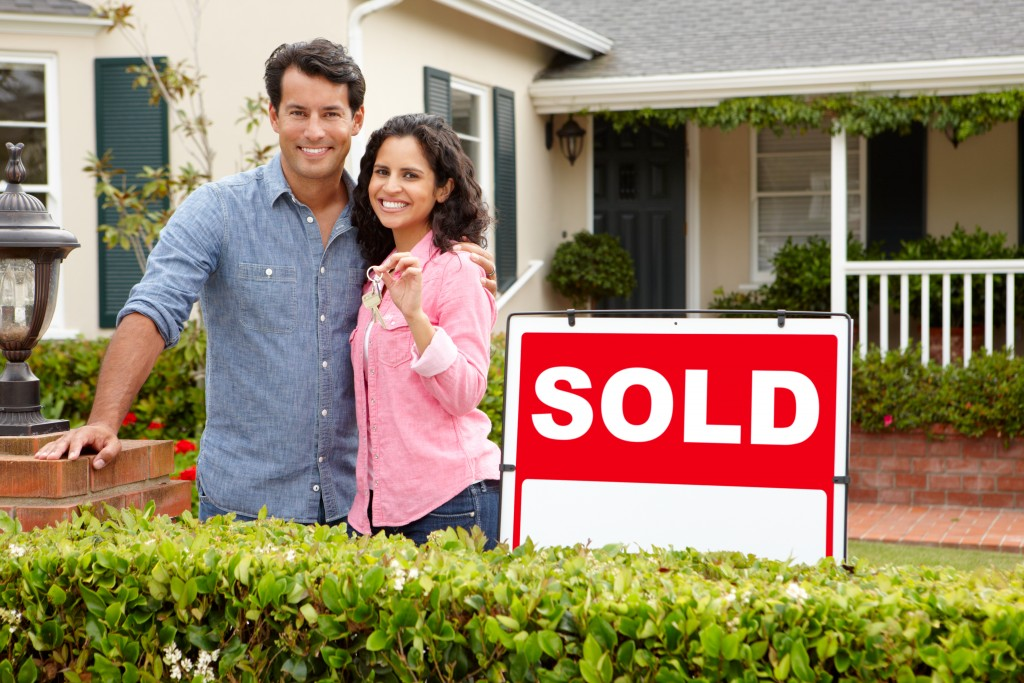 couple posing in front of the house they just bought