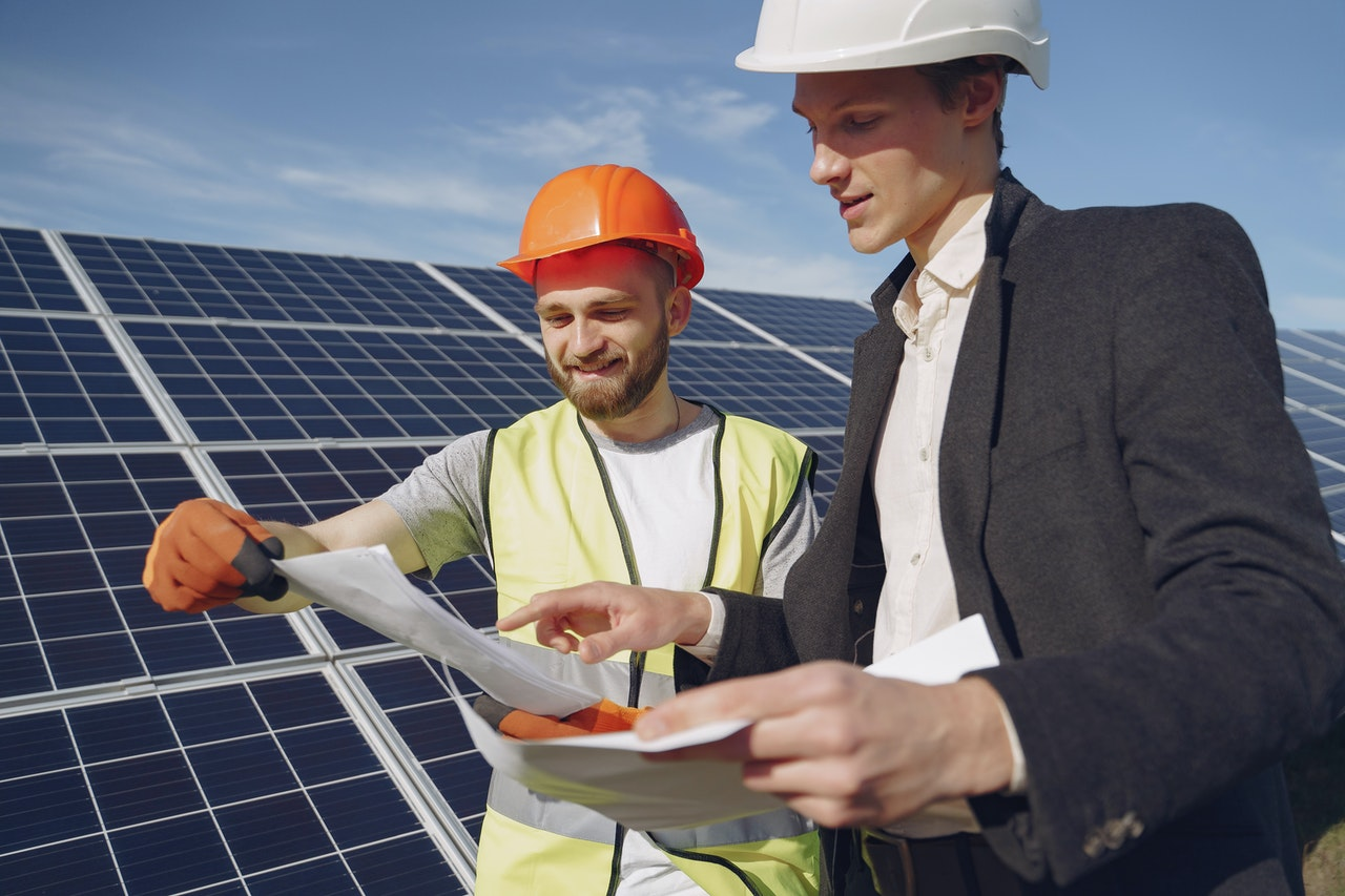 two men in front of some solar panels