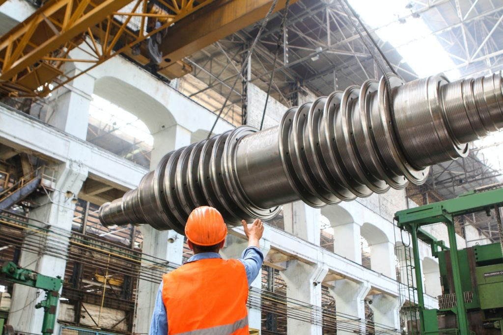 man at a factory looking at a giant metal rod