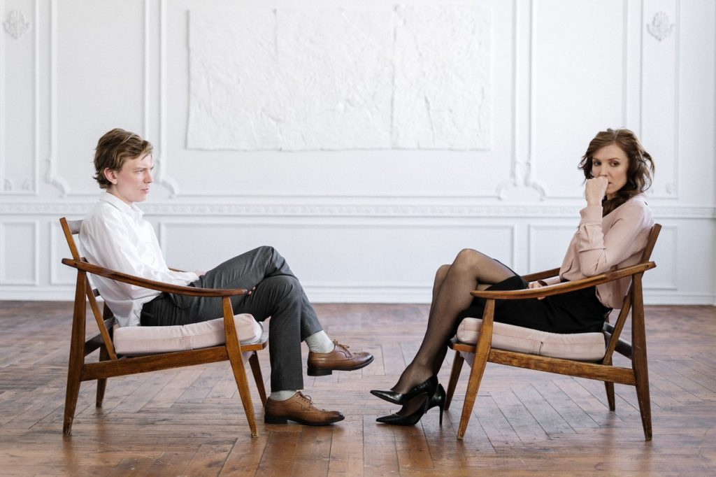 man and woman sitting across each other separation