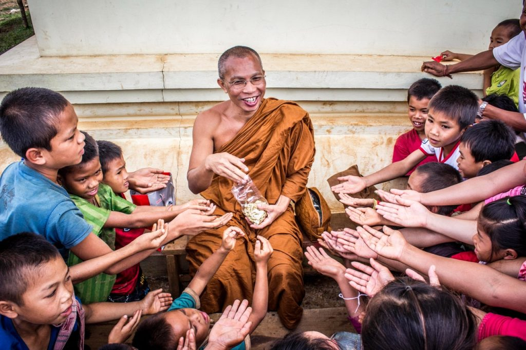 monk giving food to children