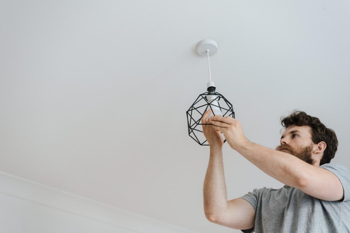 man replacing a lightbulb