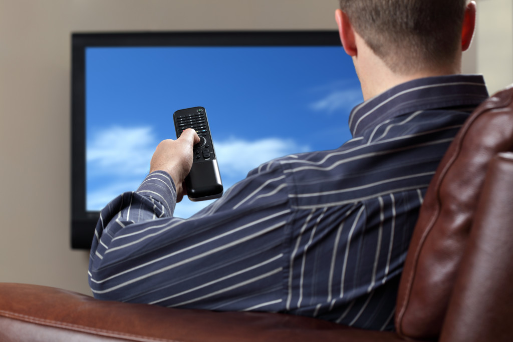 person siting on a couch, watching tv