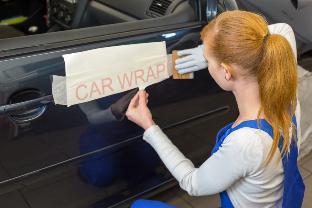 woman adding letters to vehicle